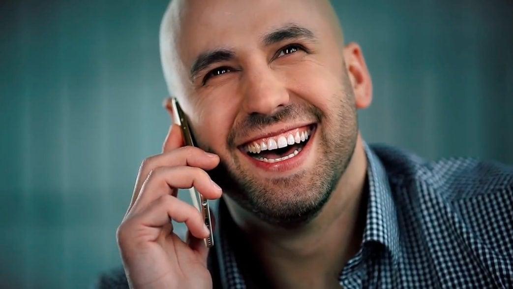 Мужчина улыбается и держит телефон. кадр из ролика для Yolla