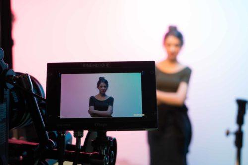 Актриса стоит в студии на фоне розового и голубого цветов