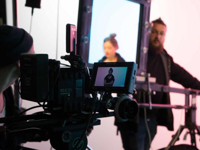 Кинокамера снимает актрису, на фоне стоит механик