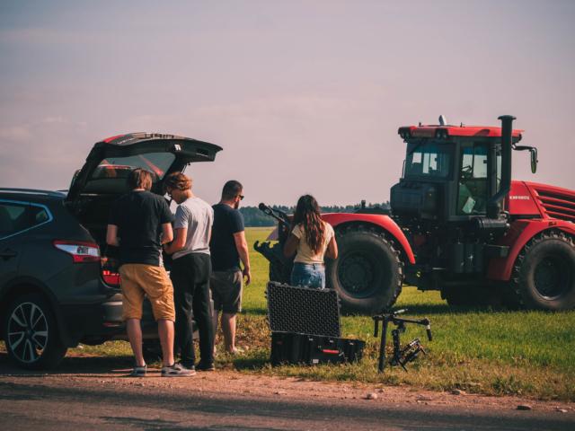 Съемочная группа стоит перед трактором Кировец