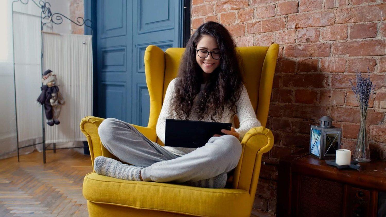 Девушка с планшетом сидит в кресле