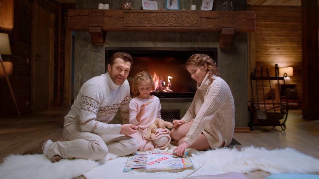 Счастливая семья сидит перед камином
